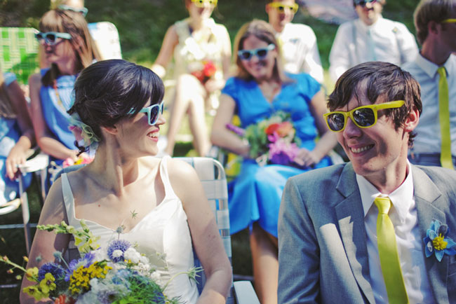 bride and groom in funky sunglasses sitting in lawn chairs