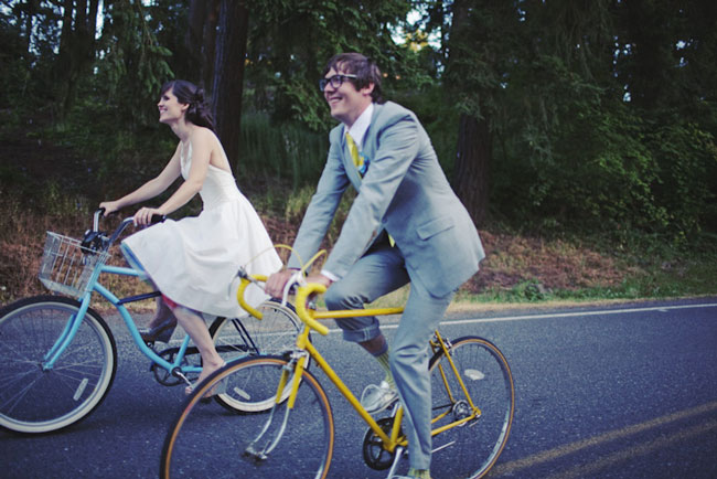 newlyweds ride colorful bicycles through forest near Hoyt Arboretum