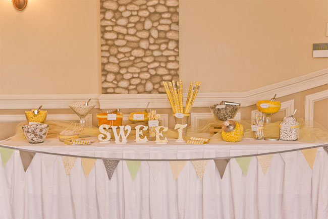 gray, mint green, and peach bunting along yellow and gray themed dessert table at wedding reception