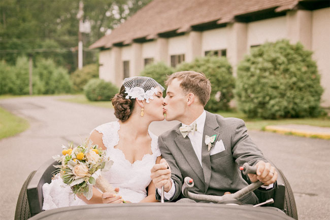Bride and groom kissing in roadster that the groom constructed. Bride wearing bird cage veil