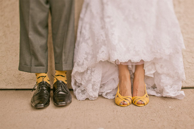Groom wearing grey pants, black dress shoes and yellow socks with black mustaches. Bride wearing yellow peep toe heels sling backs