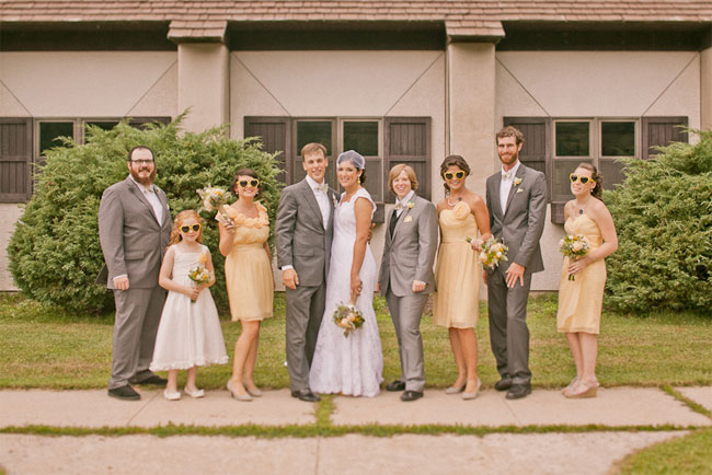 Bride and groom standing outside with bridal party. Bridesmaids wearing yellow sunglasses and yellow dresses. Groomsmen all in grey.
