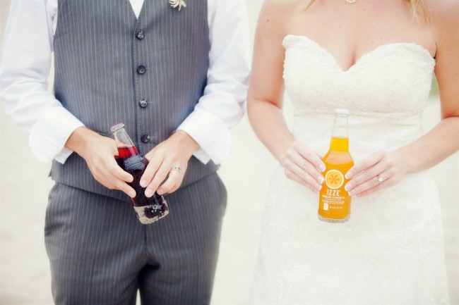 Bride and groom each holding a bottle of pop