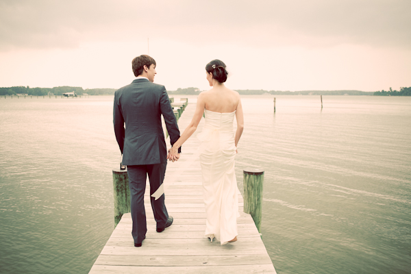 Bride and groom walking down boardwalk dock on lake in Maryland