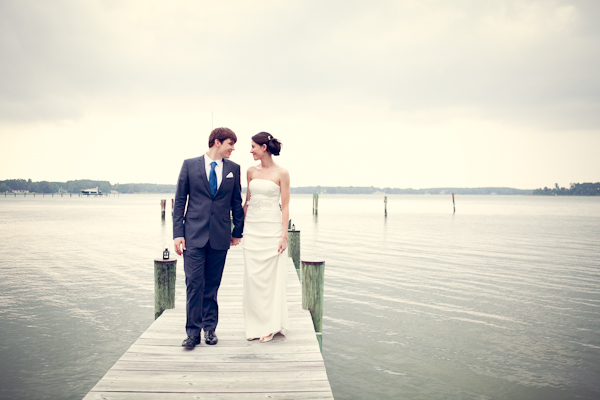 Bride and groom walking down dock.  Groom wearing dark grey suit and bride wearing white sheath gown hair in bun