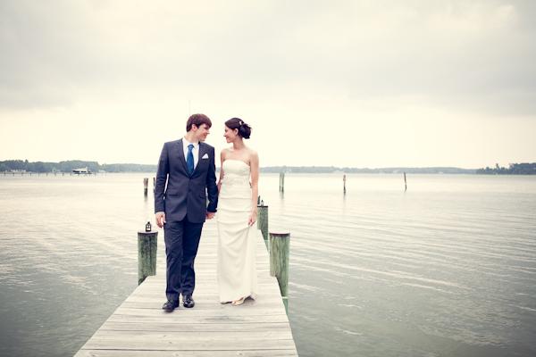 Bride and groom walking down dock. Groom wearing dark grey suit and bride wearing white sheath gown hair in bun