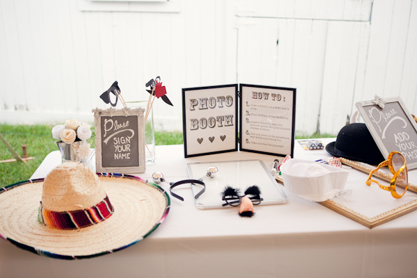Wedding reception photo booth table with sombrero, big glasses, sailor hat