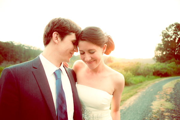 Bride wearing strapless sheath gown and groom wearing dark grey suit with blue tie standing head to head smiling on path and sun setting