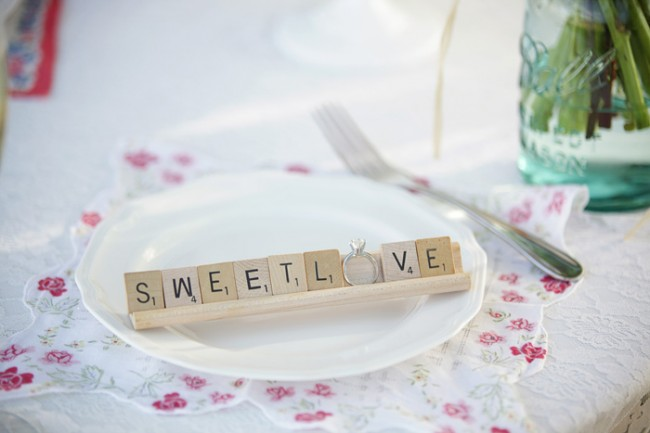 "scrabble tiles spell ""Sweet Love."" Engagement ring substituted for the letter O"
