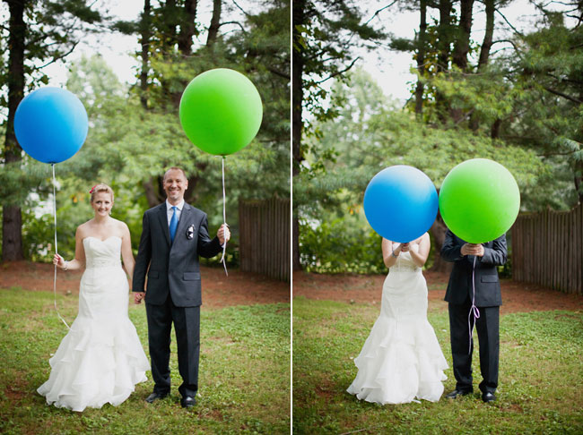 Bride holding giant blue balloon alonside groom holding giant green balloon