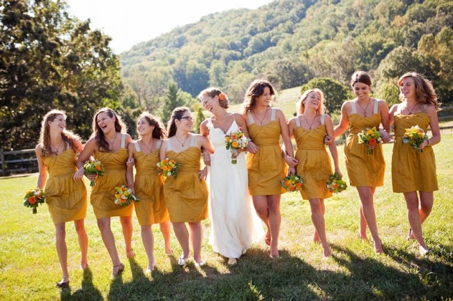 Bride walks arm-in-arm with bridesmaids in mustard yellow dresses