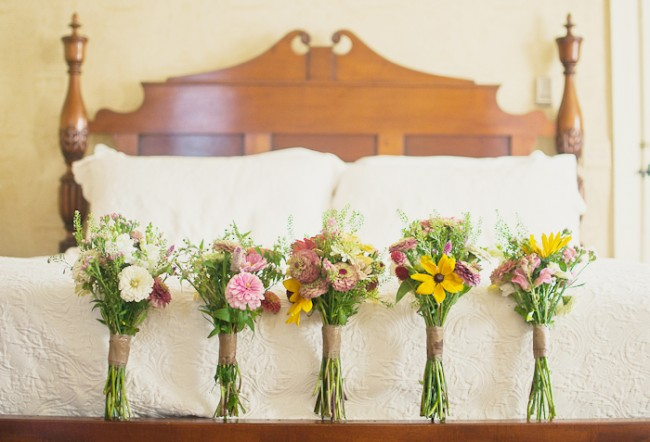5 wedding bouquets lined up on bed