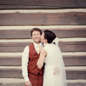 thrifty-wedding-couple-kiss-in-front-of-wood-panels