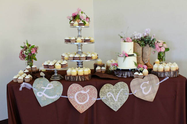 cupcake 3-tier platter with cowboy boots and cake on dessert table