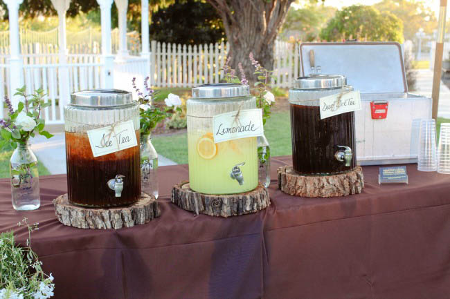 ice tea and lemonade drink containers on wood slabs