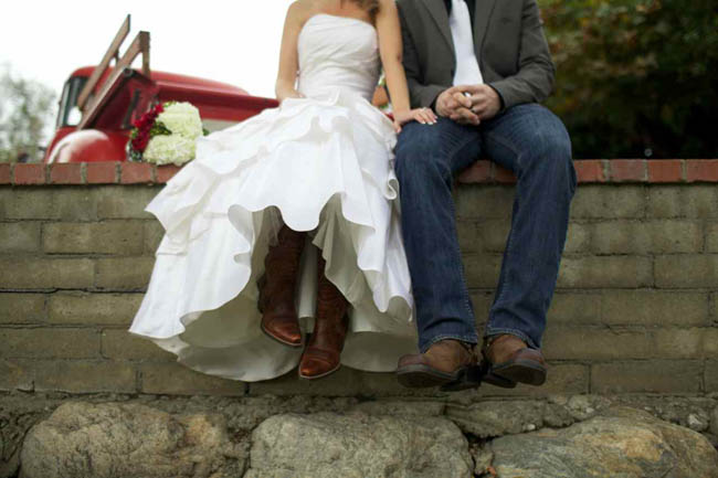 bride and groom sit on brick wall