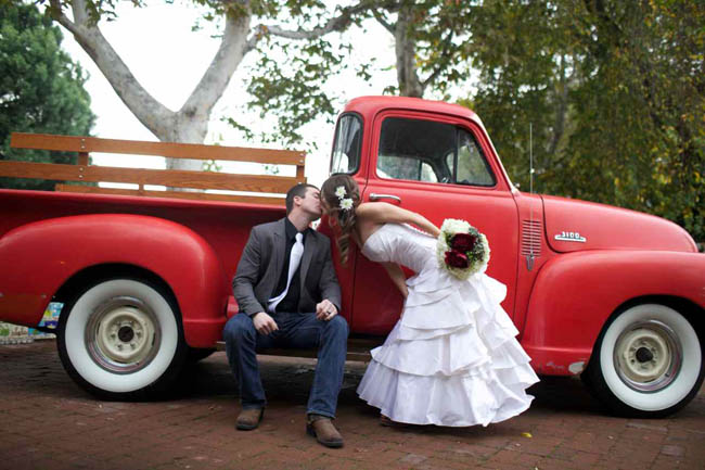 bride and groom sharing a kiss by the little red truck!