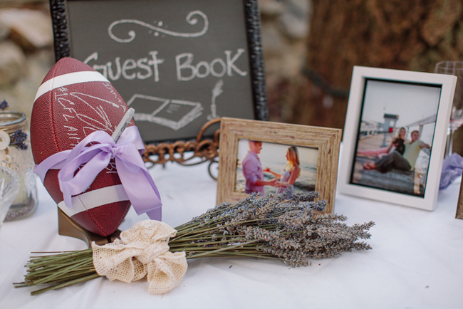 football wrapped in ribbon with lavender and photos on guest book table