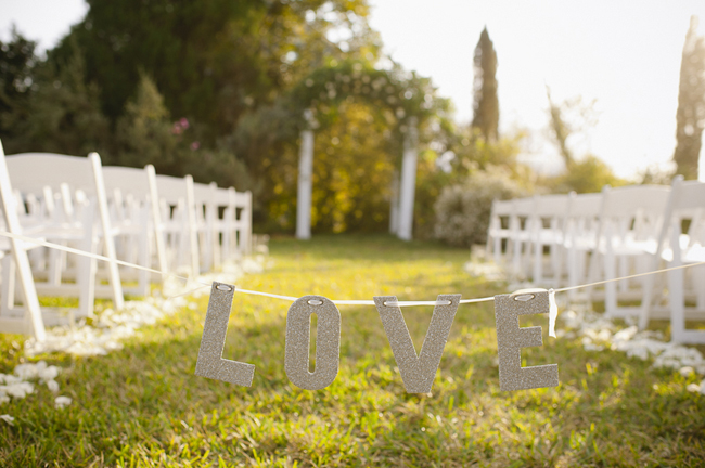 """Love"" sign strung between chairs at outdoor aisle"