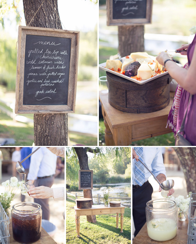 chalkboard menu sign hanging from tree trunk, cheese plate and drinks on table