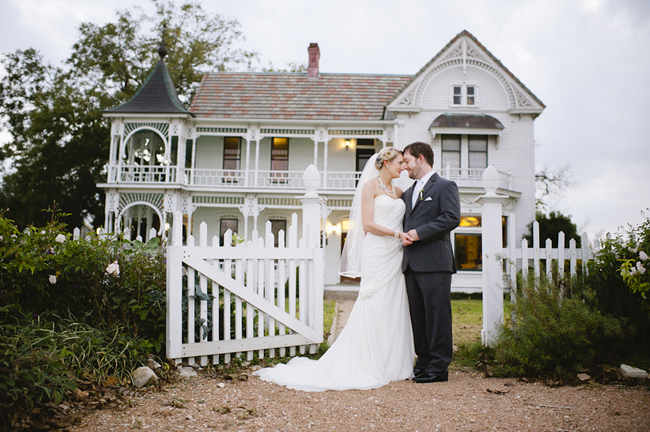 newlyweds stand at gate in front of Barr Mansion