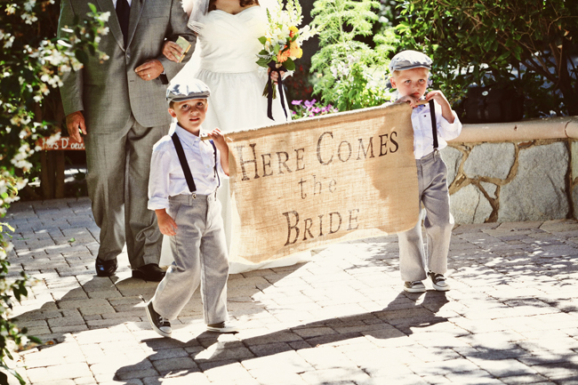 "boys in newsboy caps and suspenders carry burlap sign, ""Here comes the bride"""