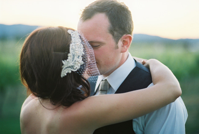 bride and groom kiss among vineyards at Eden Vale Winery