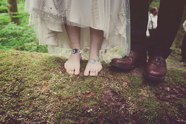 barefoot bride and groom with shoes stand on moss covered log