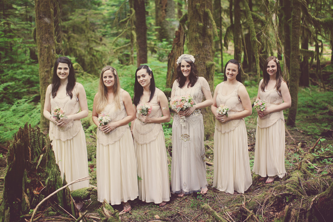 bridesmaids in light color dresses stand in old growth Washington forest
