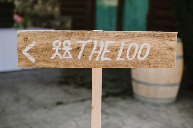 wood sign pointing to the loo