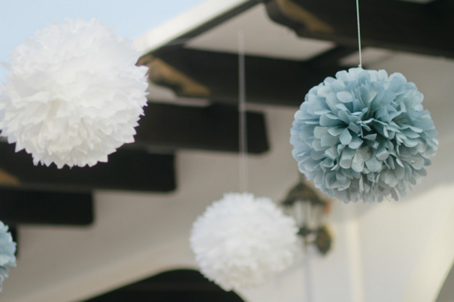 Giant hanging white and light blue pom poms at Quinta Casa Blanca wedding in California