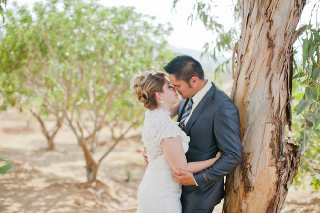 bride and groom about to kiss leaning against a tree