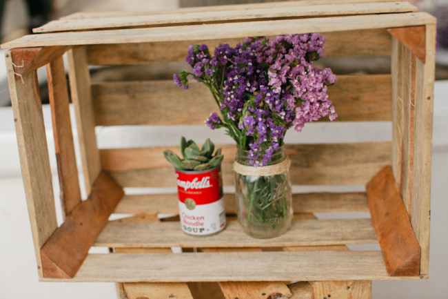 wood crate with wedding decor - purple flowers and campbell's tin can holding succulents
