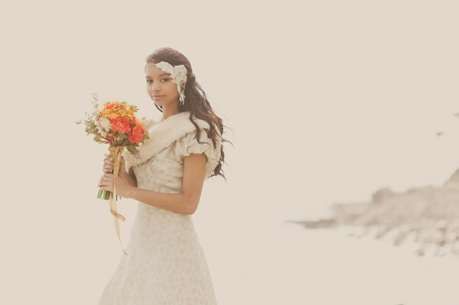 gorgeous styled shoot bride on beach holding orange and red bouquet