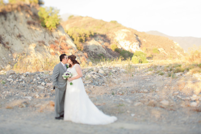 Bride and groom kiss on gravel road in California landscape