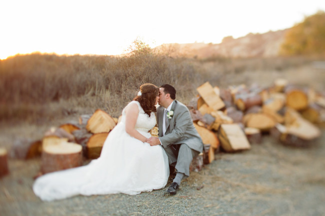 bride and groom kiss at sunset while sitting on cut tree logs