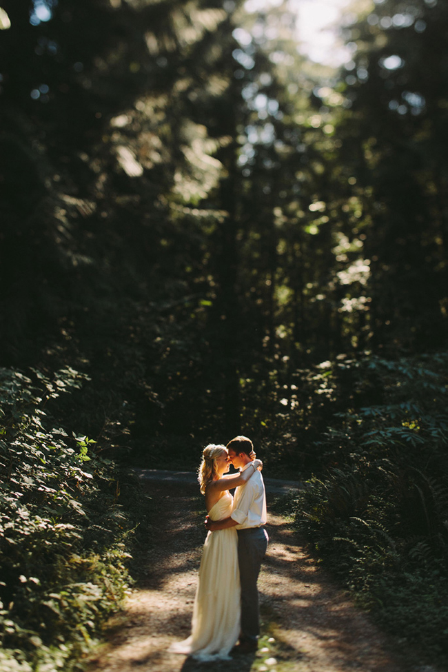 bride and groom embrace alone in the woods