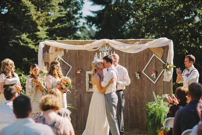 outdoor wedding ceremony with woodsy backdrop and chandelier