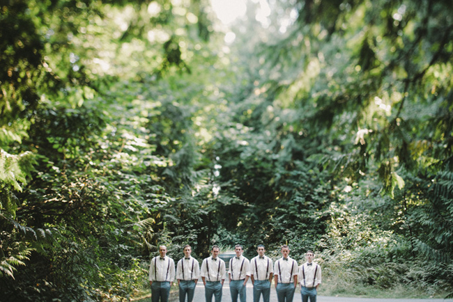 groomsmen wearing suspenders in a row among trees