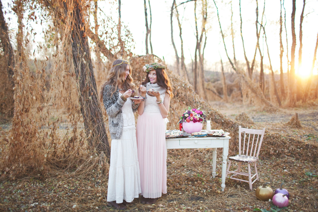 two models in bohemian dress eat pie in woods