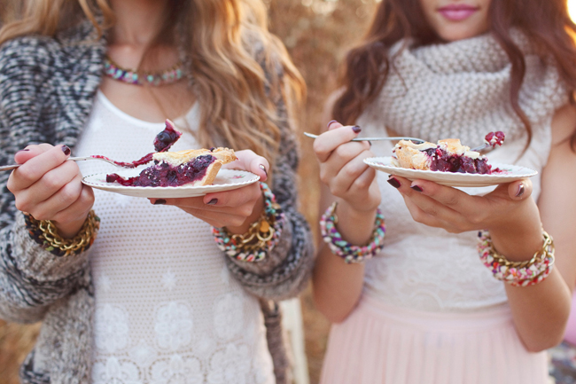 models hold plates and fork eating blackberry pie slices