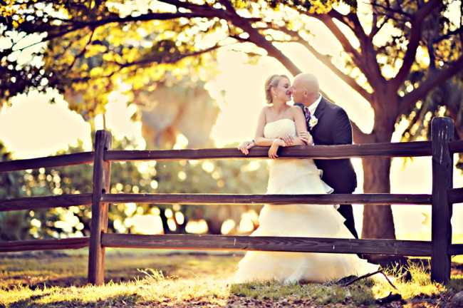 Bride and Groom kiss leaning on wood fence at Olowalu Plantation House wedding