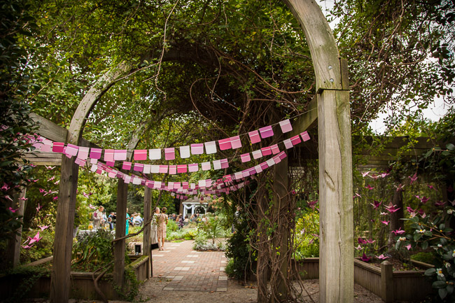 paint chips bunting hangs on wooden arbour at Klein-Pringle White Garden wedding ceremony