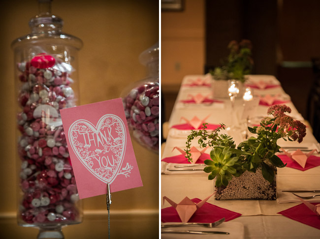 red, white, and pink M&Ms in glass jar with pink paper cranes on reception table setting