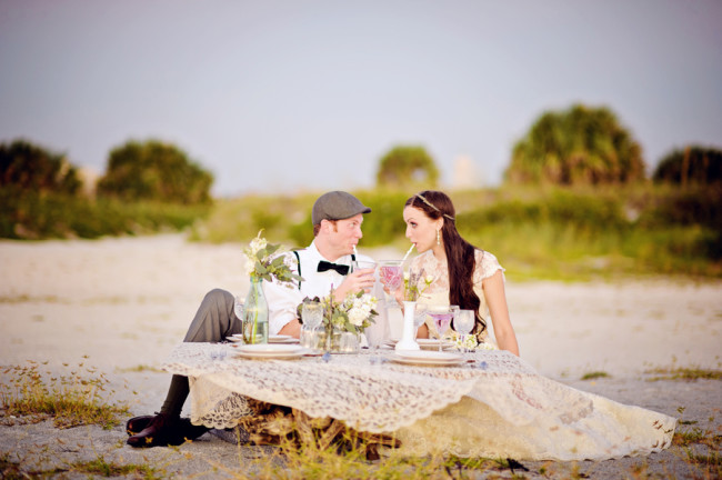 bride and groom sit on sandy Don Cesar Beach Resort at lavender theme styled shoot