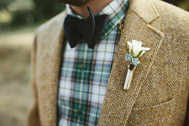 groom in dark colored bowtie, plaid shirt, jacket, with mini rose boutonniere