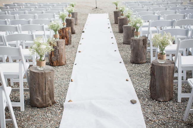 outdoor wedding ceremony with white aisle runner and log stumps with flowers on top as aisle markers