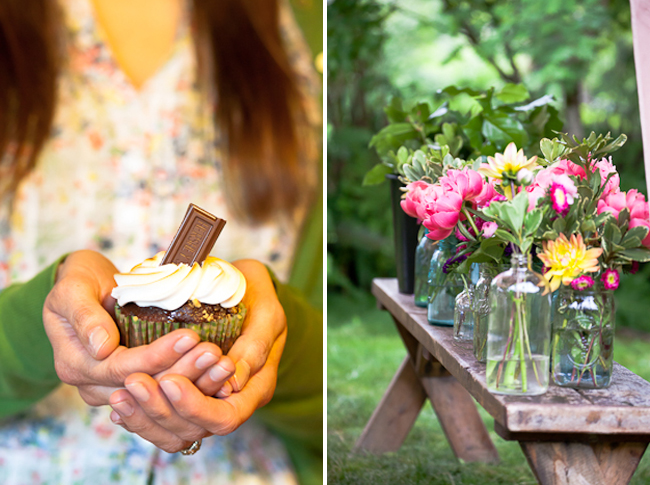 closeup photo holding chocolate cupake with piece of chocolate sticking out, flowers in clear bottles