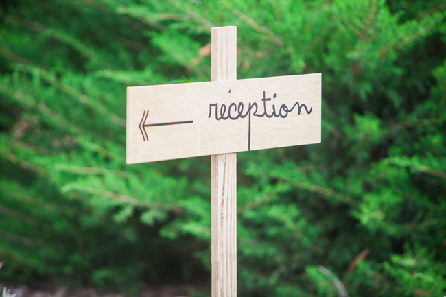 "wood stake arrow sign with the word ""reception"""