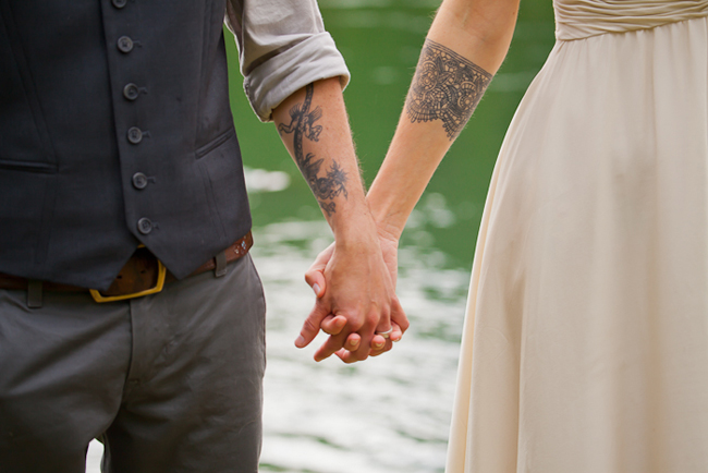 tattoos on bride and groom standing next to lake